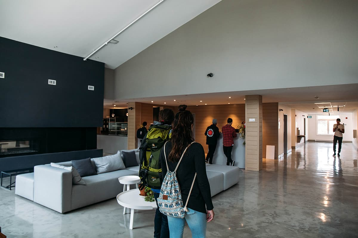 an image of the main lobby at the HI Jasper Hostel. with couches and people walking through