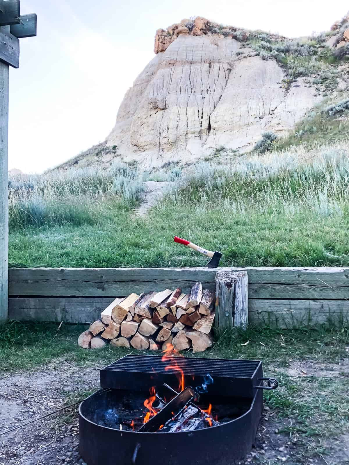 A campfire with stacks of firewood in the background